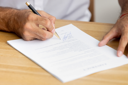 Close up caucasian male hands holding pen singing business paper, contract sitting at desk. Confirmation and accepting collaboration or hiring employment agreements, lease mortgage, insurance concept