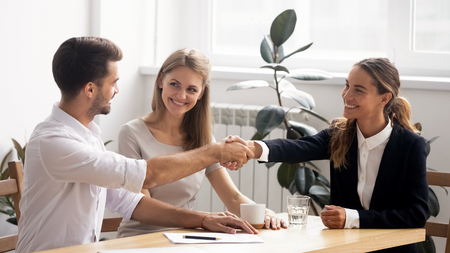 Excited smiling caucasian business people handshaking greet each other at formal meeting. Satisfied male and female partners shake hands after successful negotiation or hiring and signing contract