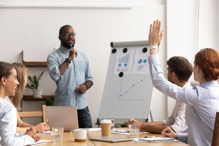 Caucasian female employee interrupts african american male mentor giving flipchart presentation for company interns. Black business mentor listening to question. Discussion coaching conference concept