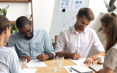 Happy smiling diverse businessmen putting signature on paper document sitting at table front of two caucasian business partners in office. Successful completion of partnership negotiations concept Stock Photo