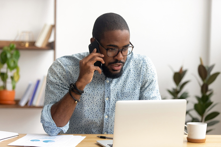 Serious african-american employee making business call focused on laptop at workplace. Black businessman consulting customer, discussing financial report. Contract negotiation and discussion concept
