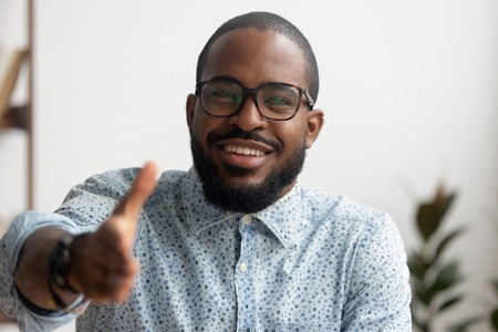 Portrait of smiling African American businessman offering hand for greeting. Friendly black employee ready for handshake, welcoming client, coworker or partner. Successful deal, introduction concept Banco de Imagens - 124259893