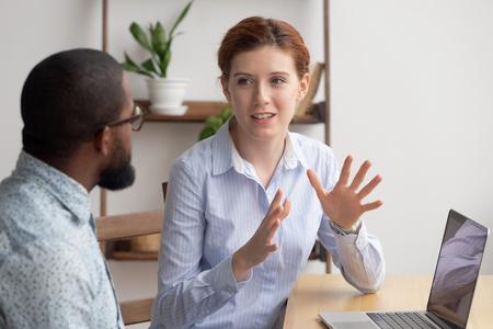 Dwóch różnych przedsiębiorców na czacie siedzi za laptopem w biurze. Podekscytowana kaukaska kobieta dzieląca się pomysłami lub biznesplanem startupowym z czarnym współpracownikiem. Nieformalna rozmowa, koncepcja przerwy w pracy