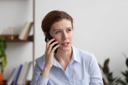 Image of concentrated businesswoman talking on mobile phone. Close up millennial employee make business call consulting customer, asking question to client of company. Communication business concept