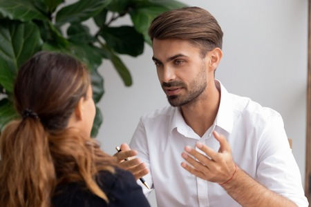 Two businesspeople talking focus on excited brainstorming caucasian employee. Man telling ideas female teammate sharing information experience. HR manager interviewing job candidate, teaching trainee