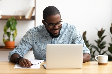 Smiling african-american manager sitting at office desk using laptop looking at screen. Handsome man reading good news, making funny video call, chatting social network. Coffee break concept