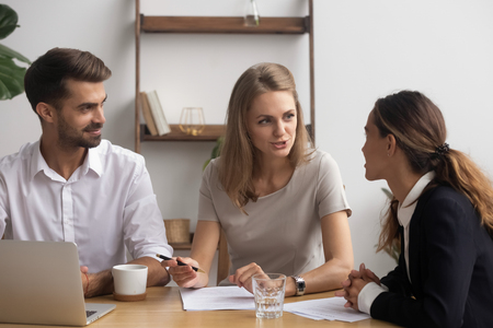 Satisfied professional company staff negotiating sitting together in office feeling good. Businesswomen businessman take break having informal talk discussing project sharing ideas finding solution Stock Photo