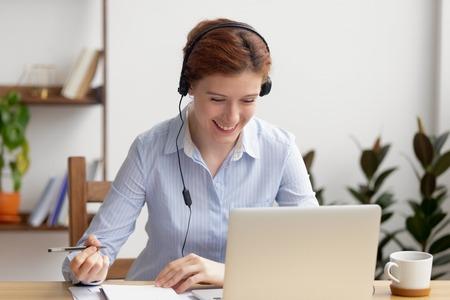 Glücklich lächelnde Geschäftsfrau mit Kopfhörern, die am Schreibtisch sitzt und sich im Selbststudium beschäftigt. Attraktive Frau, die Online-Kurse genießt, am Webinar zur Selbstverbesserung teilnimmt und Notizen macht Standard-Bild