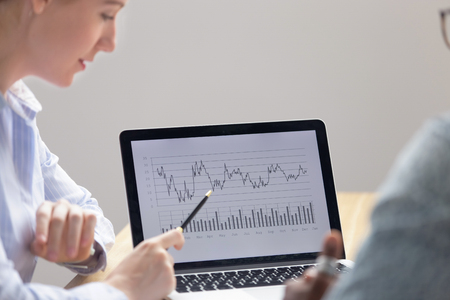 Close up caucasian female employee showing project results in graphs pointing pen on laptop. Worker explaining business strategy reporting sharing financial idea or marketing plan to black male boss