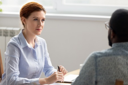 Business owner boss interviewing male black job candidate in office. Female executive manager attentively listening having good first impression. Human resources management, workforce search concept