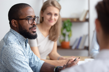 Excited male african-american talking to coworkers timeout in office informal partners conversation. Black manager telling interesting story, sharing news, business strategy. Blur background