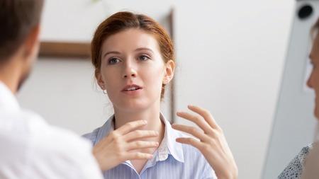 Head shot confident businesswoman, senior teacher mentor, coacher speaking to business people. Female speaker making offer, giving advice, teaching interns, sharing project idea, brainstorming