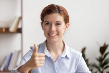 Glückliche lächelnde Geschäftsfrau des Porträts, die sich Daumen am Arbeitsplatz zeigt. Attraktiver zufriedener Geschäftsführer, der am Schreibtisch sitzt und Kamera betrachtet. Guter Job, erfolgreiches und produktives Arbeitskonzept