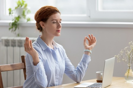 Young pretty businesswoman meditating, doing breathing exercises in office. Employee practicing yoga relaxation at workplace, rest from laptop and paper overwork. Mindfulness development stress relief
