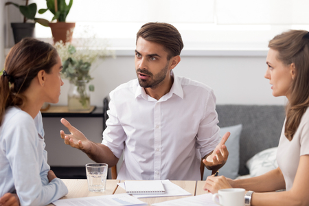 Angry businessman arguing with female subordinate at group meeting. Dissatisfied executives having conflict about paperwork failure, bad work results, default in duties. Business conflict concept Stock Photo