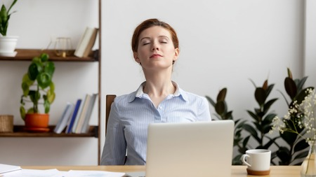 Businesswoman breathing, stretching shoulders after hard work feeling discomfort at office desk work. Young tired woman take minute pause keeping eyes closed. Uncomfortable chair, overwork on laptop Stockfoto