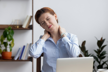 Head shot unhappy businesswoman frowning and massaging tired painful neck sitting at office desk. Upset employee feeling neckache from long time laptop work. Incorrect posture or uncomfortable place Stockfoto
