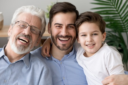 Portrait of happy little son, father and grandfather sit on couch hugging posing for family picture together, smiling three generations of men embrace look at camera laughing rest on sofa at home Stock Photo