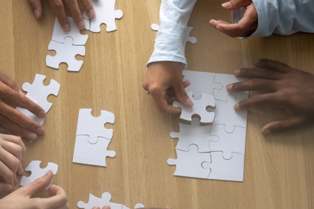 Top above close up view multiracial human hands assembling puzzle together on desk. Good teamwork and successful partnership, help and support, search right solution and business strategy concept