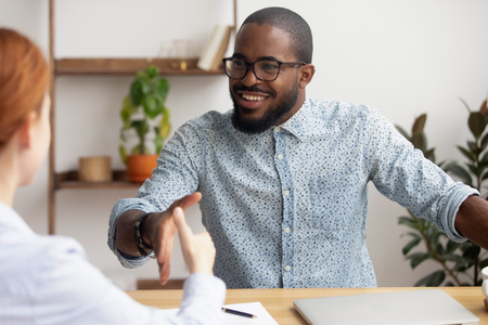 Two multiracial business partners handshaking focus on african-american employee making successful deal. Black male owner boss congratulating caucasian female candidate with new job career advancement
