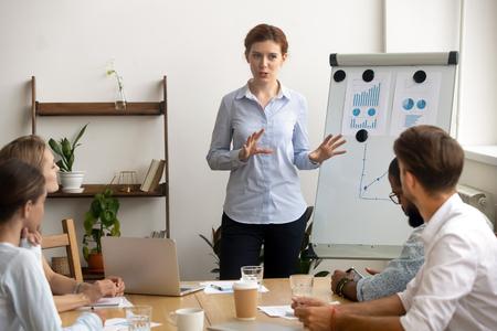 Ervaren ambitieuze zakenvrouw geeft presentatie op teamvergadering staande door flip-over. Opgewonden businesscoach in gesprek met divers publiek over bedrijfsstrategie, financieel succes, statistieken