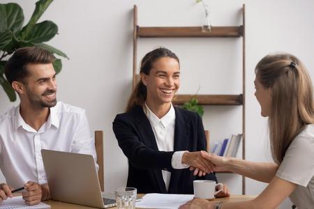Glimlachende vrouwelijke senior HR-agent die de hand schudt en de kandidaat feliciteert met een succesvol begin- of eindgesprek. Baaseigenaar begroet nieuwkomer of collega met afspraak in carrière of deal maken