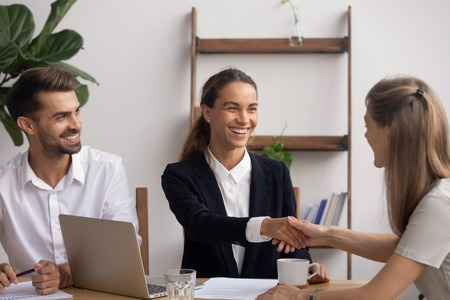 Smiling female senior HR agent shaking hand congratulating candidate with successful start or end interview. Boss owner greeting newcomer or colleague with appointment in career or making deal
