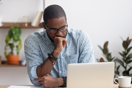 Head shot serious puzzled African American businessman looking at laptop screen sitting in office. Executive managing thinking received bad news keeping fist at chin waiting hoping positive result Stok Fotoğraf