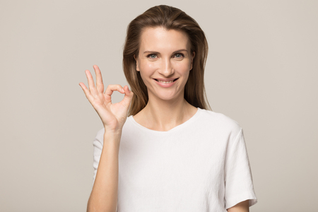 Beautiful young Caucasian woman isolated on grey studio background hold finger at lips ask be silent quiet, millennial female look at camera tell share mystery, announce secret sale or discount