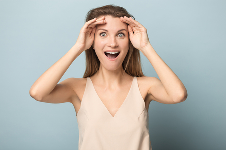 Smiling young woman isolated on blue studio background cover eyes with hands ready for surprise, happy millennial female close face excited to see unexpected thing or good news announcement