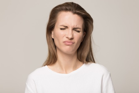 Unhappy Caucasian millennial woman isolated on grey studio background frown feel disappointed or displeased, upset disappointed young female look at camera show discontent or complaint