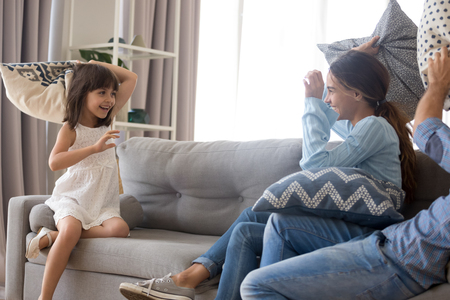 Excited young family have fun at home engaged in pillow fight together, cute preschooler girl enjoy childish game with playful parents, mom and dad spend time entertaining with little daughter