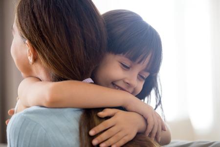 Nahaufnahme eines süßen kleinen Mädchens, das junge Mutter oder Kindermädchen umarmt, die Liebe und Fürsorge zeigen, glückliches Kind im Vorschulalter umarmt Mutter danke oder bittet um Vergebung, lächelnde Eltern und kleine Tochter kuscheln sich versöhnen Standard-Bild