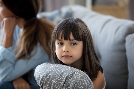 Sad cute little girl sit alone feel lonely lack parent attention, upset preschooler daughter hug pillow need mom love and care, mother and daughter feel offended unhappy on couch. Family drama concept