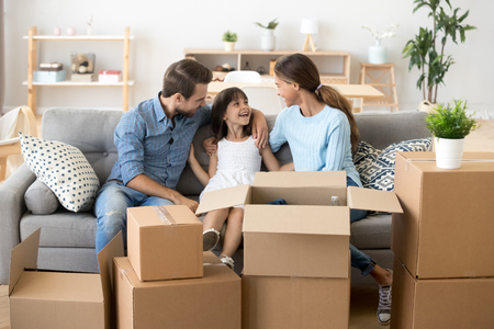 Happy young parents sit on cozy couch with small smiling daughter relaxing on moving day, excited family have fun talking spend time together rest on sofa relocating to new house. Relocation concept 스톡 콘텐츠