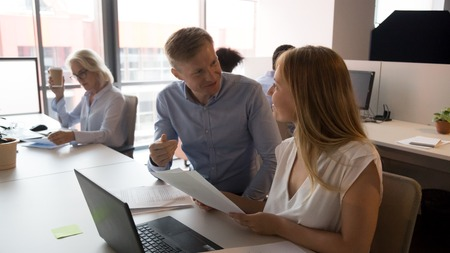 Confident businessman mentor helping female intern with paperwork, trainer consulting trainee, colleagues having pleasant conversation, discussing financial report, working on project together Banco de Imagens