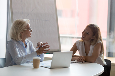 Mature businesswoman mentor talking with female intern in boardroom, explaining task to trainee, discussing business strategy, staff training concept, brainstorming, employee consulting client