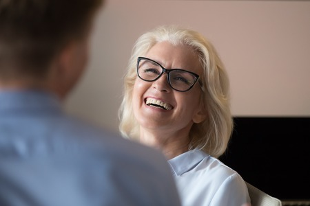 Attractive mature businesswoman laughing at colleague joke during break, pause, employees having pleasant conversation, discussion funny news, having fun in office, exited by success, close up