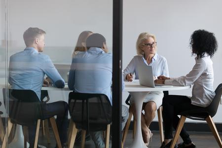 Mitarbeiter, die dem afroamerikanischen Teamleiter bei der Sitzung im Sitzungssaal zuhören, Geschäftsleute, die gemeinsam die Geschäftsstrategie diskutieren, Personalschulung, Partnerverhandlungskonzept