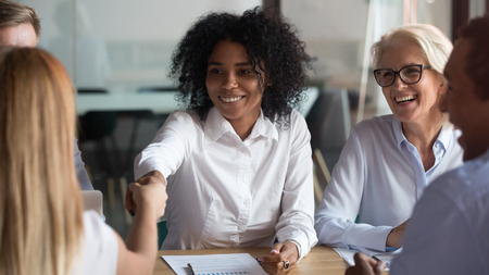 Smiling African American businesswoman shaking hand of business partner at meeting, greeting, getting acquainted, boss congratulate subordinate with promotion, thanking for good work result Stockfoto