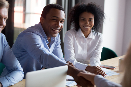 African American businessman shaking hand of business partner at meeting, greeting, getting acquainted, congratulate with promotion, thanking for good work result, successful deal, contract signing