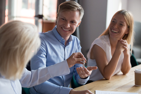 Smiling man receiving keys from new house, making deal with realtor in office, tenants signing lease agreement with mature manager, taking loan or mortgage, client purchasing property, real estate