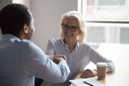 Smiling mature businesswoman shaking hand of African American colleague, greeting, getting acquainted with new employee during coffee break, smiling hr manager handshaking with job applicant Stockfoto