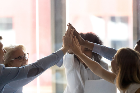 Close up diverse employees giving high five at company meeting in boardroom, showing unity, motivation for better teamwork result, team celebrating success, great business result at briefing