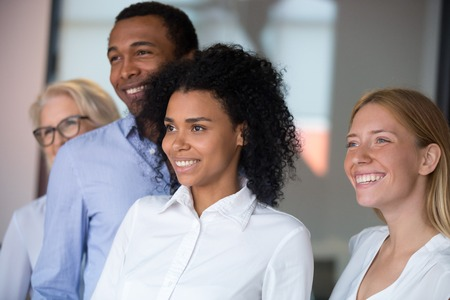 Head shot of excited diverse employees with African American leader posing in office, smiling successful boss standing with multiracial company staff, looking away, photographing together close up Reklamní fotografie