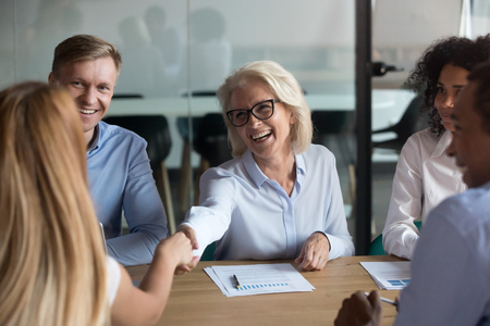 Smiling mature businesswoman shaking hand of business partner at meeting, greeting, getting acquainted, team leader, boss congratulate subordinate with promotion, thanking for good work result Stockfoto