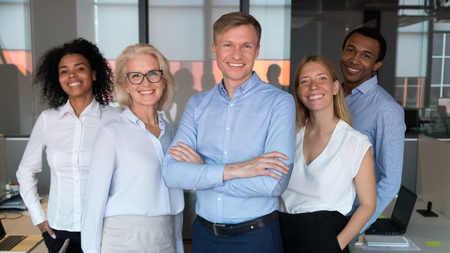 Successful team leader and diverse employees posing for photo together, smiling businesspeople looking at camera, standing in modern office, feeling proud, multiracial company staff photo