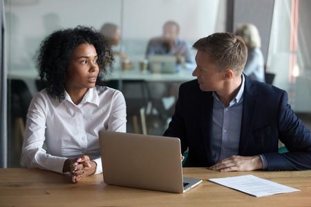 Mentor de hombre de negocios confiado que da instrucciones al aprendiz en el lugar de trabajo, ayuda al nuevo empleado con el proyecto en línea, verifica los resultados, gerente ceo con entrevista de trabajo con el solicitante afroamericano