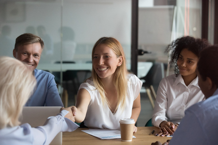 Attractive businesswoman shaking hand of business partner at meeting, greeting, getting acquainted, female team leader holding briefing with multiracial employees, thanking for good work result Stockfoto