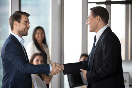 Happy businessmen handshake greeting get acquainted at formal meeting in office, smiling male business partners shake hands closing deal, congratulate with successful negotiation. Cooperation concept